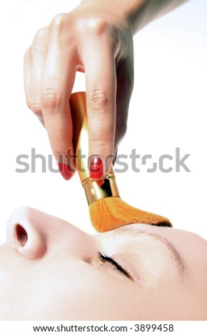 girl is having a make up treatment with powder brush - stock photo