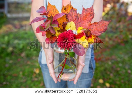 Girl is holding a bunch of leaves of mountain ash, maple, red and  daisies hrizontem. Bunch is in the pot with water. Bouquet close-up shot. The photo was taken at sunset autumn sun in the garden.