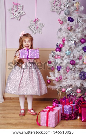 Girl is holding a Christmas present. The emotion of joy. New Year. Holiday and fun. Merry Christmas. 2017 - stock photo