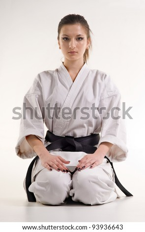 girl is in a kimono.punch.figure in the karate fighting stance on a white background - stock photo