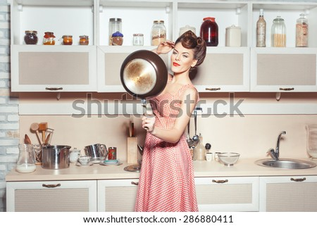 Girl is in the kitchen. She straightens her hair. She looks in the pan like a lady in the mirror. - stock photo
