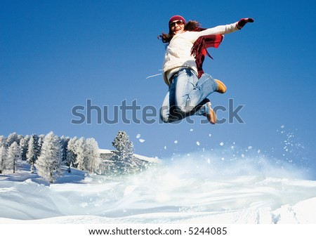girl is jumping in the snow.