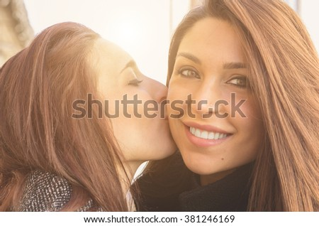 Girl is kissing her friend on her cheek - caucasian people - stock photo