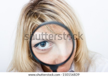 Girl is looking through a magnifying glass - stock photo