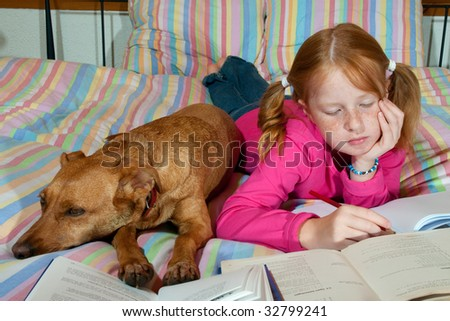 Girl is making homework together with her dog - stock photo