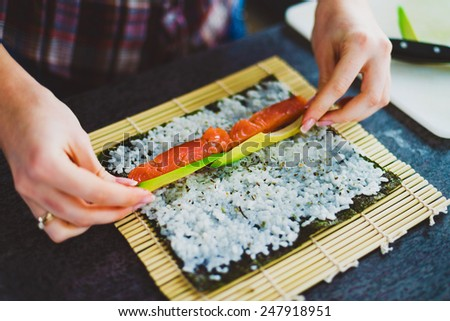 girl is making sushi at home - stock photo