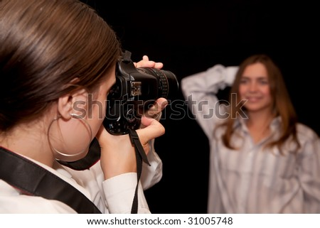 Girl is photographing a model against black background. Focus on camera
