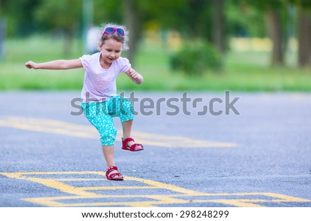 Girl is playing hopscotch game on the asphalt - stock photo