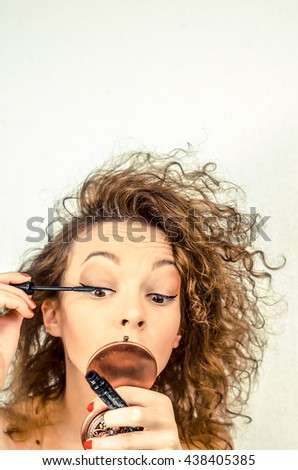 girl is preparing to go out and put mascara on the eyes, the girl is introduced into their work with makeup