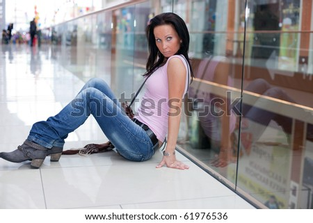 Girl is relaxing on the floor in the shopping mall - stock photo