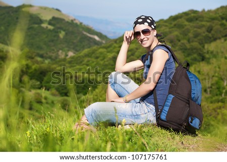 girl is resting sitting on the green grass in the mountains
