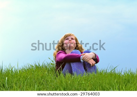 Girl is sitting in the grass, looking up to the sky - stock photo