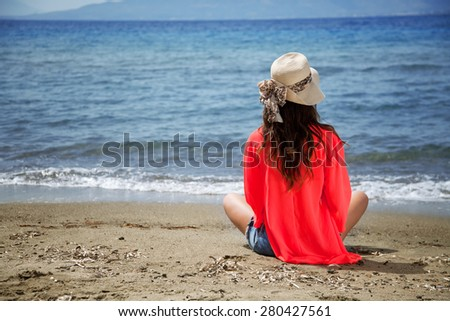 Girl is sitting near the sea and waiting for something - stock photo
