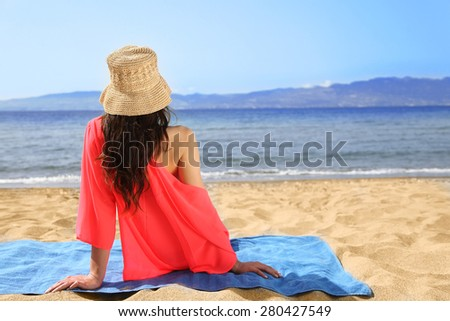 Girl is Sitting on a Towel At the Beach - stock photo