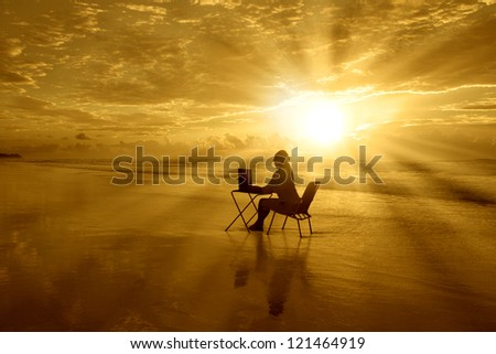 Girl is sitting with her laptop under beautiful sunset on the beach - stock photo