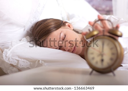girl is sleeping and turns off the alarm at 6 am - stock photo