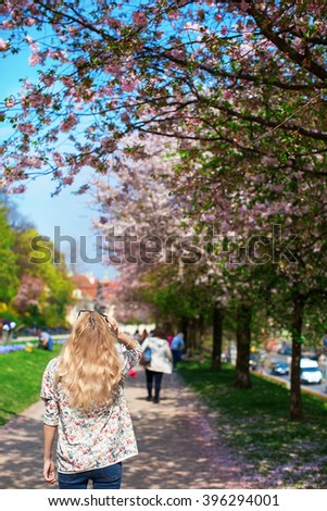 girl is standing back on the street with flowering trees