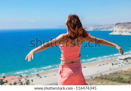 Girl is standing on rock and looking at sea. Her hands are raised up