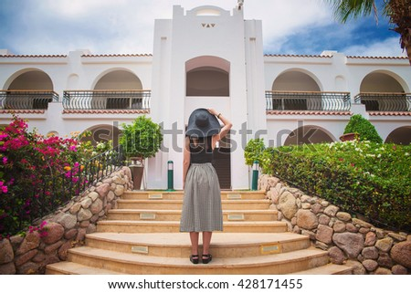 girl is standing on the steps in front of the big house - stock photo