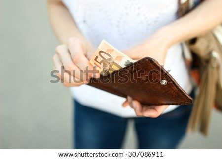 Girl is taking out a banknote of fifty euros from brown leather wallet on the street. Hands, money and wallet close-up.  - stock photo
