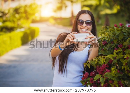 Girl  is talking a photo on the phone - stock photo