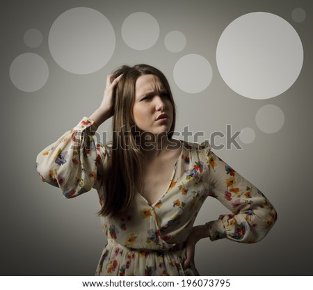 Girl is trying to remember something. Forgetfulness concept. Grey bubbles in the background. - stock photo
