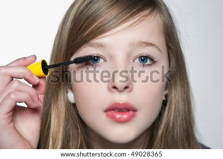 Girl is using a mascara for her first makeup. - stock photo