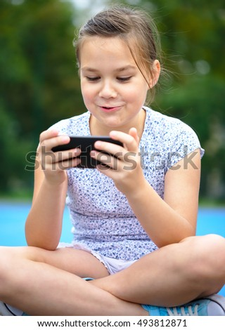 Girl is using smartphone, outdoor shoot