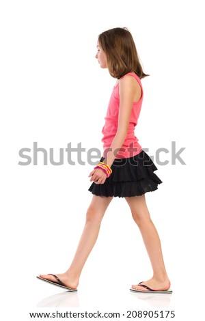 Girl is walking in slippers and mini skirt, side view. Full length studio shot isolated on white. - stock photo