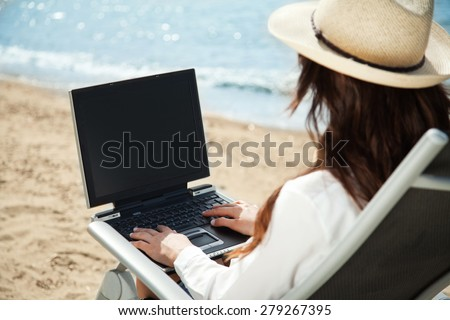 Girl is working at the beach - stock photo