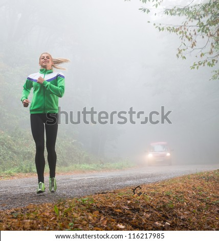 girl jogging in autumnal woodland with fog - stock photo