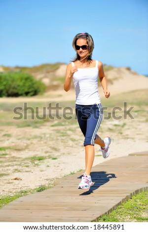 girl jogging on the beach - stock photo
