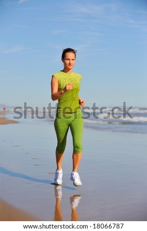 girl jogging on the beach at sunrise - stock photo