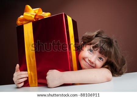 girl joyously embraces the gift of sitting at the table - stock photo