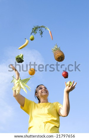 Girl juggling fruits and vegetables - stock photo