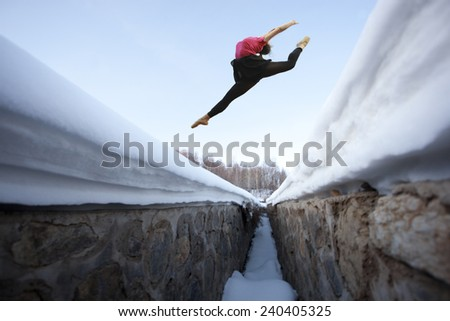 girl jump high over snow mountain in winter season - stock photo