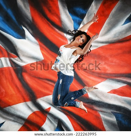 girl jumping and flying on the background of the British flag - stock photo