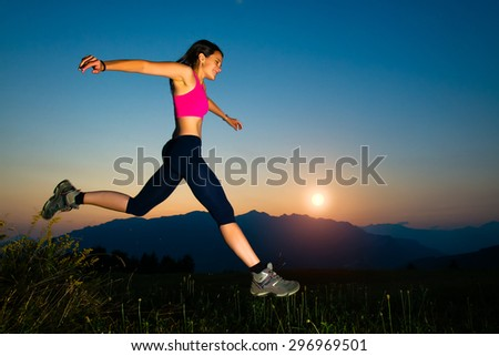 Girl jumping at sunset in the mountains