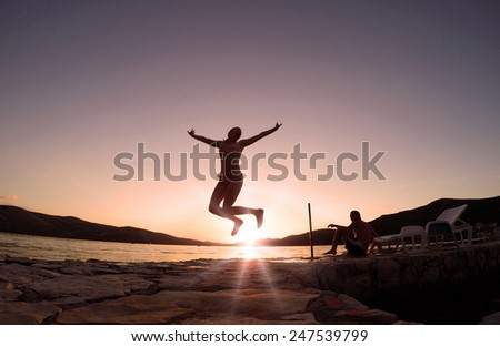 Girl jumping at sunset on the beach - stock photo