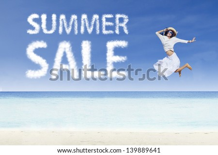 Girl jumping beside summer sale cloud on white sand - stock photo