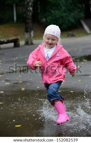 girl jumping in puddles  - stock photo