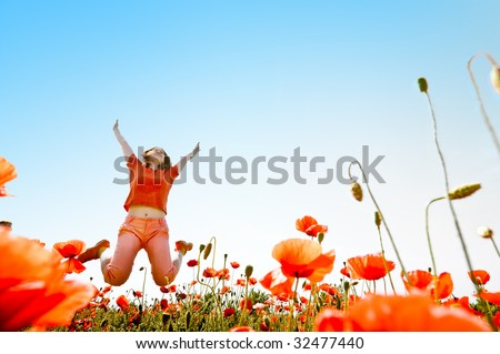 girl jumping in red poppies field - stock photo