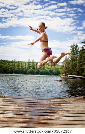 girl jumping off a dock into a lake - stock photo