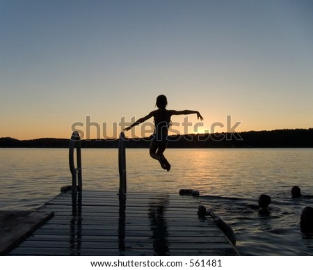 Girl jumping off a pier at dusk - stock photo
