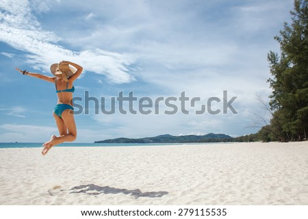 Girl jumping on a tropical beach at summer, rear view - stock photo