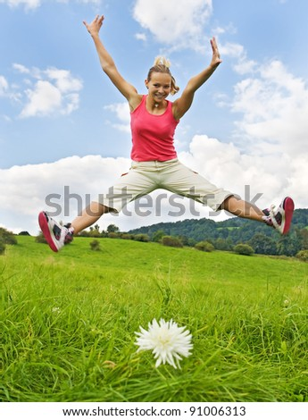 girl jumping on meadow - stock photo