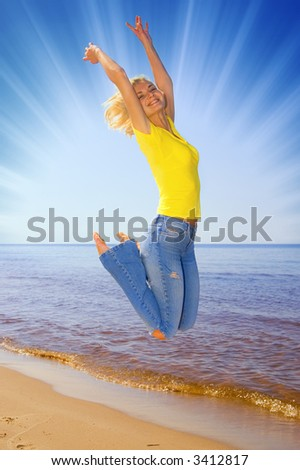 Girl jumping on the beach - stock photo