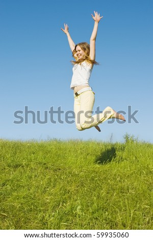 Girl jumping on the green meadow