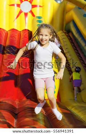 Girl jumping on the trampoline in amusement park