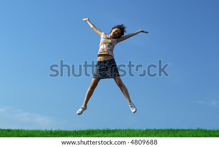 Girl jumping over a green grass - stock photo